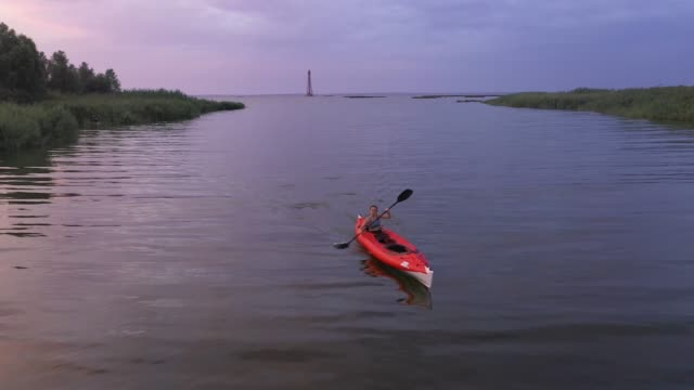 Scenic aerial view of a woman kayaking to  lighthouse at sunset