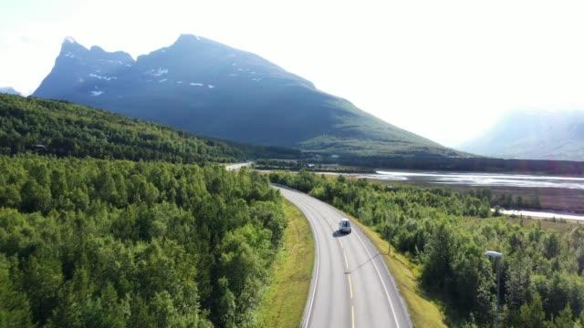 vídeos de stock e filmes b-roll de scenic aerial view of car on  road in norwegian countryside - noruega