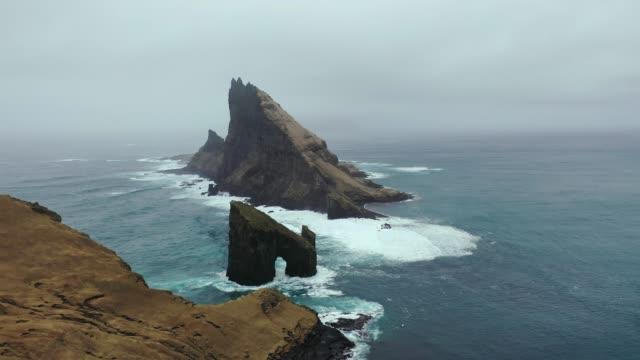 stockvideo's en b-roll-footage met scenic aerial view van drangarnir arch in faeröer - rocks sea