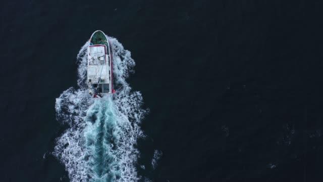 vídeos de stock e filmes b-roll de scenic aerial view of fishing boat   in lofoten islands in winter - reine