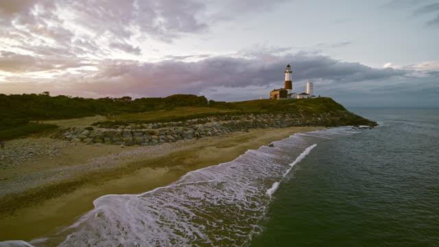 malerische luftaufnahme von montauk leuchtturm bei sonnenuntergang. long island, new york state, usa - leuchtturm stock-videos und b-roll-filmmaterial