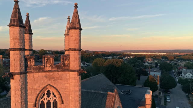 scenic aerial view of nazareth, pennsylvania, with his churches at sunset. aerial drone video with the forward camera motion. medieval-style st john united church of christ in the main focus. - горы поконо стоковые видео и кадры b-roll