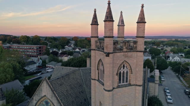Scenic aerial view of Nazareth, Pennsylvania, with his churches at sunset. Aerial drone video with the forward camera motion. Medieval-style St John United Church of Christ in the main focus.