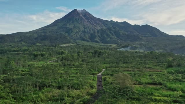 Scenic aerial view of old fashioned SUV on the background of Merapi volcano