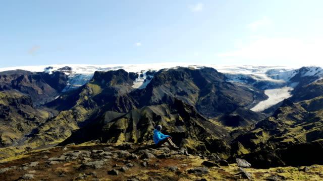 stockvideo's en b-roll-footage met mooie luchtfoto van vrouw op zoek naar kleurrijke bergen van landmannalaugar in ijsland - geologie