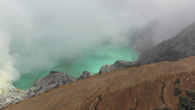 Scenic aerial view of woman looking at  Ijen volcano and sulphur minings