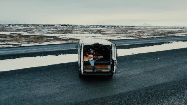 Scenic aerial view of woman  playing guitar  in camper van Scenic aerial view of young Caucasian  woman  playing guitar  in camper van rv interior stock videos & royalty-free footage