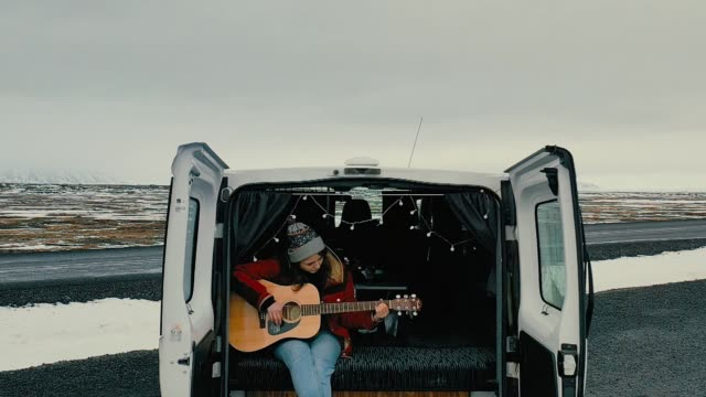 Scenic aerial view of woman  playing guitar  in camper van