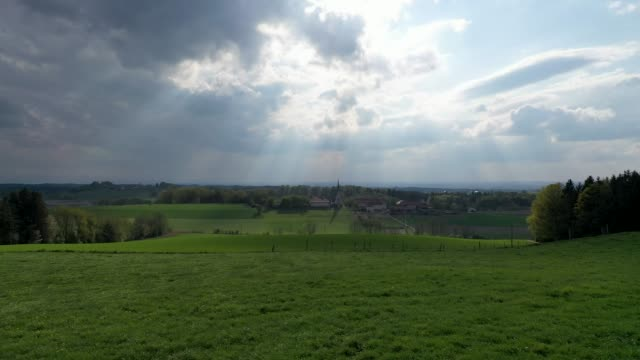 scenic arial panoramic view of a bavarian idyllic village next to green rolling hills and forest, the sun is shinig through the clouds right on top of the church (near to bavarian alps) - paesaggio collinare video stock e b–roll
