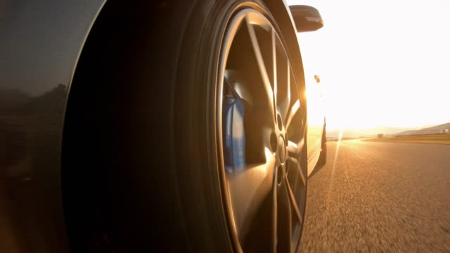 Scenic car drive at sunset Scenic car drive at sunset, view of sports car front wheel spinning tires stock videos & royalty-free footage