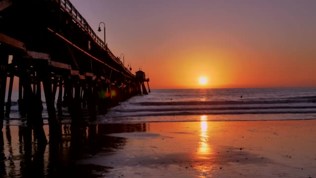 Scenic orange pink Sunset with epic rays of light and sun flare wooden pier in San Clementa California