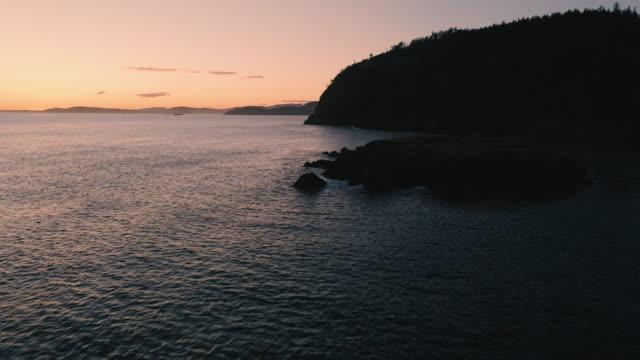 残光照明によるロッキー沿岸海岸シルエットの風光明媚な太平洋北西部空中 ビデオ