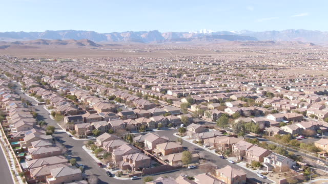 drone: scenic shot of las vegas suburbs sprawling across the mojave desert - città diffusa video stock e b–roll