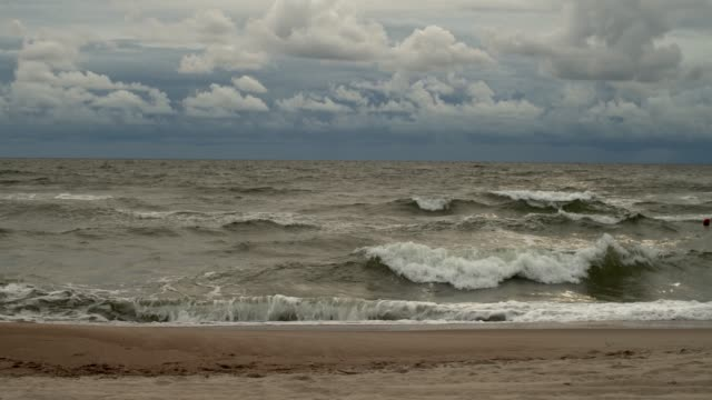 Scenic stormy seascape with big waves rolling on sandy beach Scenic stormy seascape with big waves rolling on sandy beach front view background. Sea ocean breaking out rainy storm cyclone. Dangerous season environment protection ecology care baltic countries stock videos & royalty-free footage