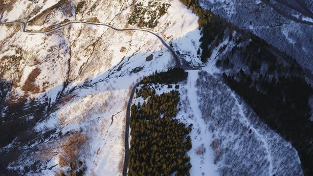 vista aerea panoramica della foresta coperta di neve e dell'autostrada curva durante il tramonto. strada attraverso la montagna, doppia pineta colorata. rallentatore - strada tortuosa video stock e b–roll
