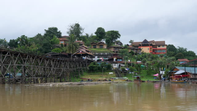scenic view of classic long wooden bridge cross large river with old community of tribe - burma home do filmów i materiałów b-roll
