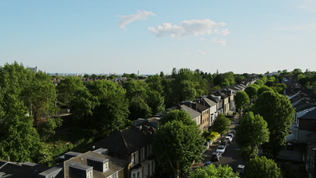 scenic view of houses and green trees at the residential terraced housing in central north london, united kingdom - aerial panning shot - nord europeo video stock e b–roll