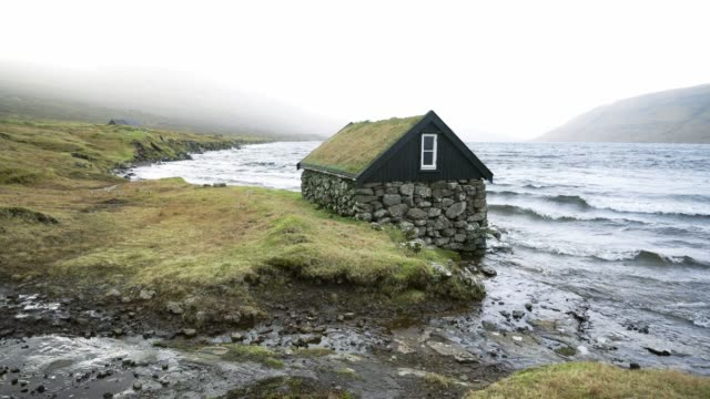 Scenic view of hut with roof covered in moss near the seaside in Faroe Islands