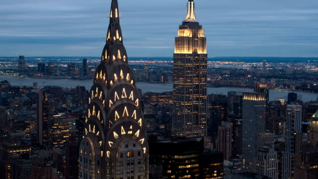 CLOSE UP, AERIAL: Scenic view of Midtown Manhattan, Chrysler Building top lit up in the dark and New Jersey in the background