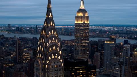 vidéos et rushes de close up, antenne: vue panoramique de midtown manhattan, sommet du chrysler building illuminé dans le sombre et nouveau maillot en arrière-plan - horizon urbain