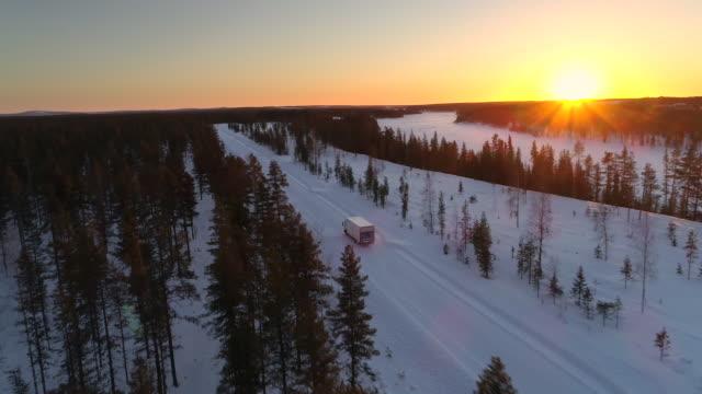 vídeos de stock, filmes e b-roll de vista panorâmica da paisagem de floresta de pinheiros e van em alta velocidade na auto-estrada nevada ao pôr do sol - viagens rodoviárias