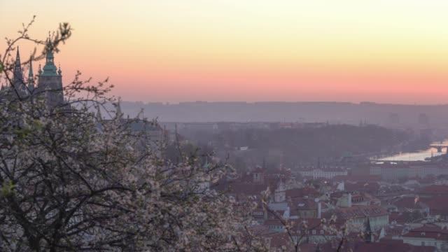 vidéos et rushes de vue panoramique des toits carrelés de prague pendant le lever du soleil au printemps. tours de st vitus et église saint-nicolas vu du point de vue de la colline de petrin. lueur de soleil d'or romantique dans le matin et arbres fleurissants dans un sta - saint nicolas