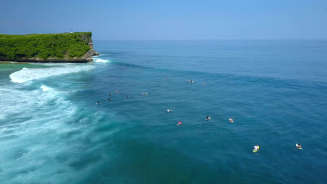 AERIAL: Scenic view of surfers lining up in the sea below a majestic rocky cliff video