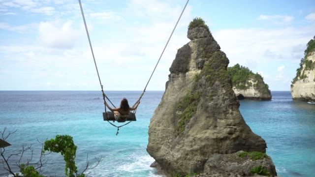 Scenic view of woman on swing above the sea on Nusa Penida
