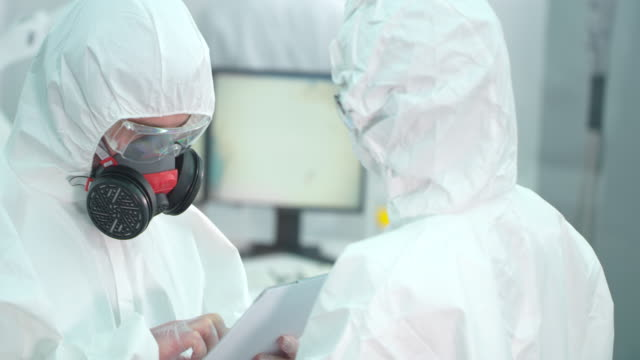 Scentists in lab wearing protective suits are talking
