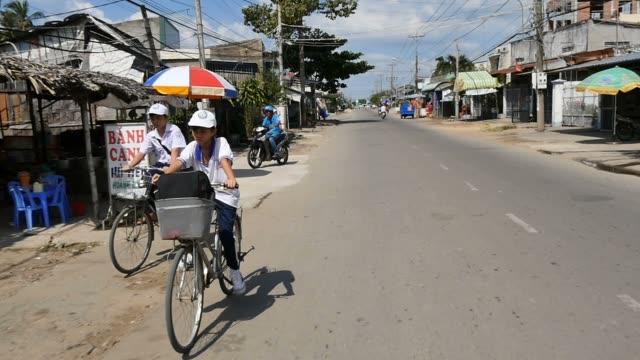 MEKONG DELTA, VIETNAM - 2015: School boy on bike riding home village lifestyle video