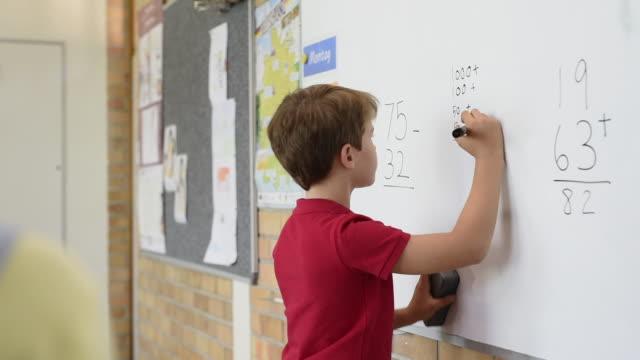 schule junge lösen mathematische problem - grundschule stock-videos und b-roll-filmmaterial