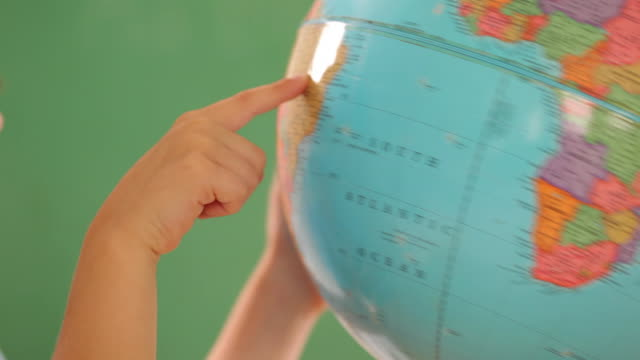 stockvideo's en b-roll-footage met school boy's hands touch globe, closeup - bureauglobe
