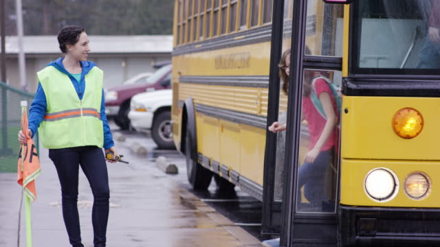 School bus attendant ushering elementary students off of bus video