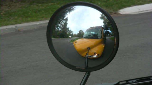 School bus reflection in rear view mirror. video