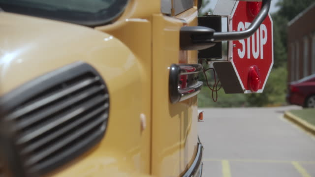 School bus stop sign opening - Dolly 1 A dolly shot of a modern yellow school bus that starts in front of the bus and moves to the side as the stop sign opens and begins flashing. school buses stock videos & royalty-free footage