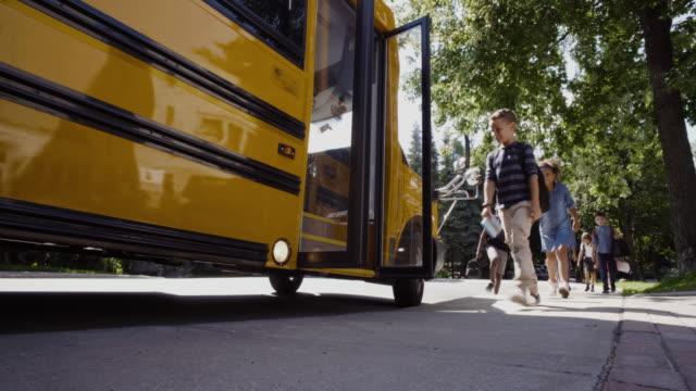 school bus student getting in 4k 4:2:2 slow motion - school buses stock videos and b-roll footage