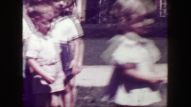 1949: School children closeup running woman teachers flower print dress. video