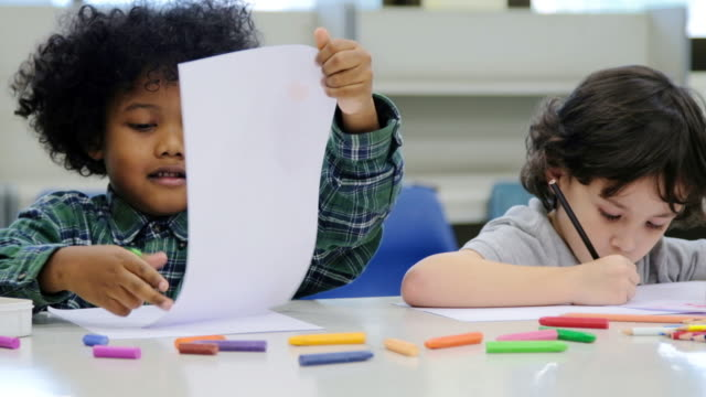 School children, happy little boys drawing with colors and crayons video