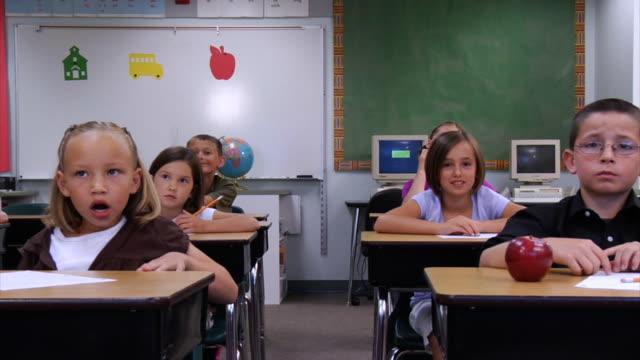 School children in classroom raising hands video
