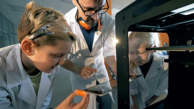 school children make the robot printing it on a 3d printer. - zagadnienia filmów i materiałów b-roll