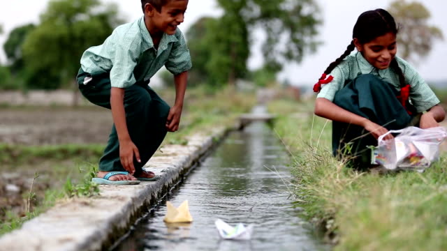 School children playing with paper boat near water canal HD1080p: School children of elementary age wearing school uniform sitting near water canal outdoor in the field & playing with paper boat. indian family stock videos & royalty-free footage