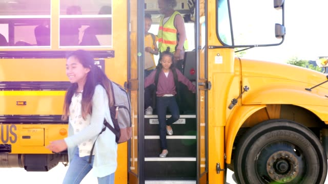 school children unload school bus - scendere video stock e b–roll