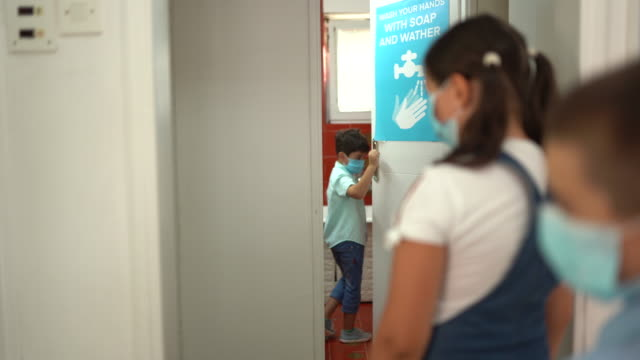 School children waiting in a line for bathroom and keeping social distancing during coronavirus pandemic