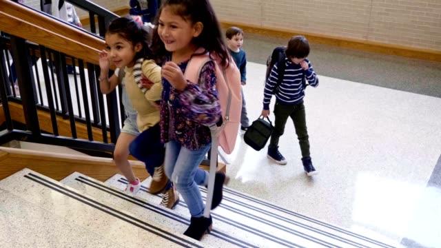 vídeos y material grabado en eventos de stock de niños de la escuela subiendo escaleras en el edificio de la escuela - escuela media