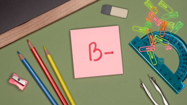 School concept. Woman writing B- (B with minus) mark on sticky notepad. School concept. Woman writing B- (B with minus) mark on sticky notepad. School supplies and stationery on the desk test results stock videos & royalty-free footage