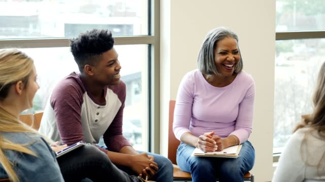 School counselor leads discussion group with teenagers Confident female school counselor discusses teenage issues with a group of teenagers. She laughs with the students as they open up to her. school counselor stock videos & royalty-free footage