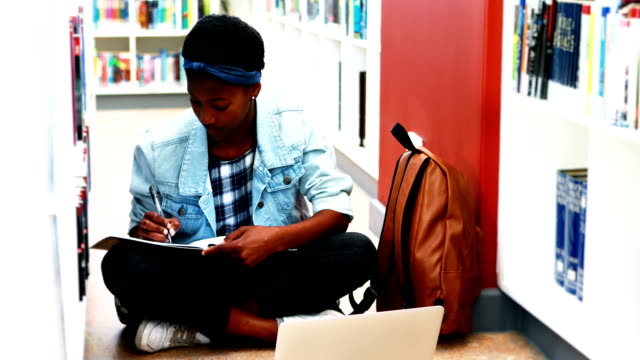 School girl doing home work while using laptop in library video
