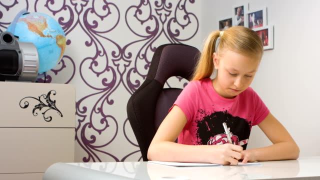 school girl doing homework - çalışma kitabı stok videoları ve detay görüntü çekimi