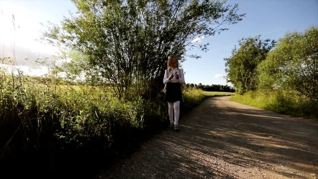 Colegiala en falda negra y camisa blanca es caminar por el camino arenoso. - vídeo
