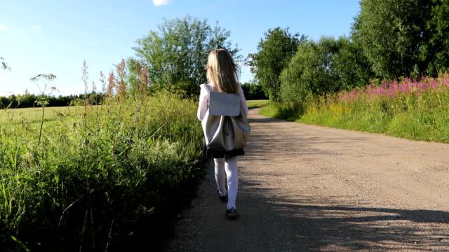 Colegiala en falda negra y camisa blanca es caminar por el camino arenoso a través del campo y bosque. Tiro de Steadicam. - vídeo